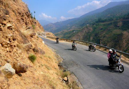 <h3>La grande traversée du Bhoutan</h3>  A la frontière terrestre avec le Bhoutan, nos motos indiennes nous attendent à Samdrunp Jongkhar pour une première étape moto de 180 Km en terre himalayenne. Pénétrer au Bhoutan par la route et sillonner le royaume d'Est en Ouest est un des plus beaux itinéraires possibles. Le Bhoutan de l'Est est un merveilleux petit paradis perdu, loin des circuits classiques. La diversité des paysages nous surprend et lorsque l'on progresse entre jungle tropicale et forêts de bambous, on se demande où sont les hauts sommets himalayens enneigés. A Trashigang, nous découvrons notre premier dzong. Ces forteresses bouddhistes sont de véritables centres religieux, politiques et administratifs, constituant l'identité de chaque ville. Le dzong de Trashigang accueille chaque année au mois d'avril un festival unique, un « tsechus ». C'est une chance d'assister au spectacle irréel des danses des moines vêtus de leurs masques colorés. L'aventure se poursuit de dzongs en dzongs jusqu'à Mongar à travers les forêts de pins. Le lendemain, une étape de 190 Km nous mène au Bhoutan central, à travers de magnifiques routes de montagne, en entamant l'ascension du deuxième col carrossable le plus élevé du Bhoutan, le Thrumshing La (3780m).