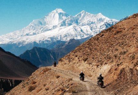 """<h3>Mustang : L'Expédition Légendaire</h3>  Longtemps appelé """"Le Royaume Interdit"""" car il était jusque récemment interdit d'accès aux étrangers, le Mustang est un ancien royaume dont la vallée forme des gorges vertigineuses parmi les plus profondes du monde. Vintage Rides vous a concocté dans cette région, de Pokhara à Jharkot, un parcours des plus exigeants. Pistes cassantes, sommets dressés à plus de 8000 mètres d'altitude : tout est au rendez-vous pour un voyage moto d'exception. Entouré par le Tibet dont l'influence est palpable partout, et protégé par les géants himalayens, le Mustang est une vraie terre d'aventure pour les motards. De cols en canyons, hommes et machines seront mis à rude épreuve pour venir à bout des étapes. Au bout du voyage, à plus de 3500 mètres d'altitude, vous aurez le privilège d'admirer l'ancien royaume dans un décor minéral majestueux."""